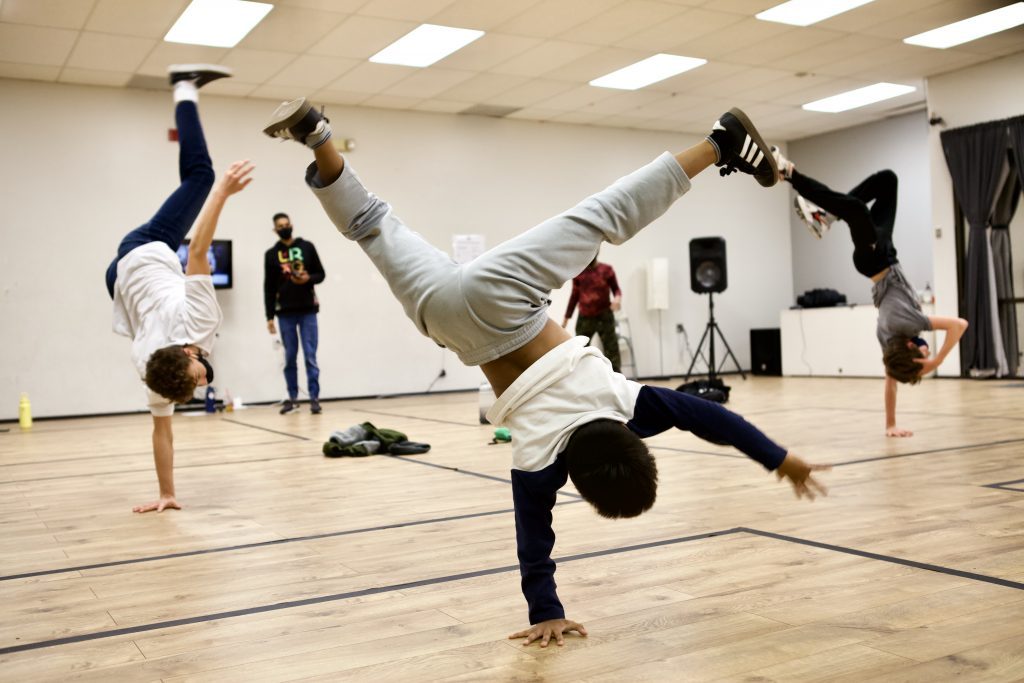 Hip Hop Breaking Students in Face Masks One-arm Hand Stand